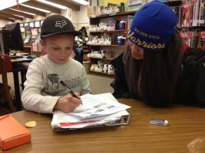 Jerica Manuel, sophomore, helping fourth grader, Seth, with his homework. (Photo courtesy of Bridget Pocasangre)