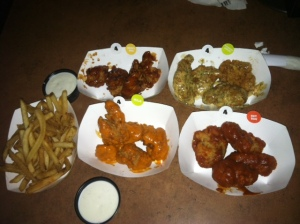 Some of the many flavors Buffalo Wild Wings offers (Honey BBQ, Parmesan Garlic, Mild and Hot BBQ) along with fries and a side of ranch.