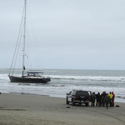 (Photo Courtesy of Jane Northrop) The Pacifica police and a group of rescue swimmers coordinate their efforts in order to reach the suspects aboard the yacht.