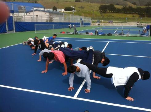 (Photo Courtesy of Shannon Randolph) The Boys Tennis team doing some team building and bonding by creating a push-up bridge.
