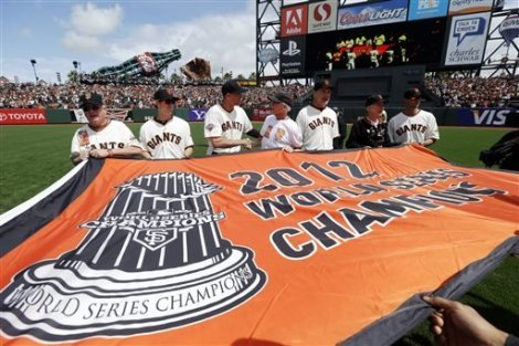 (Photo Courtesy of sfgiants.com) Some of the Giants players holding their 2012 World Series Champions flag on opening day.