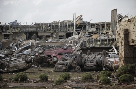 (Photo Courtesy of Brett Deering/Getty Images) Flipped vehicles are piled outside of a destroyed medical center.