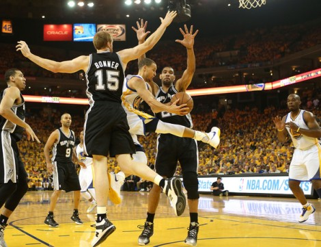 (Photo Courtesy to Zimbo) Stephen Curry driving in between Tim Duncan (#21) and  Matt Bonner (#15) dishing out to Carl Landry for an easy lay up.